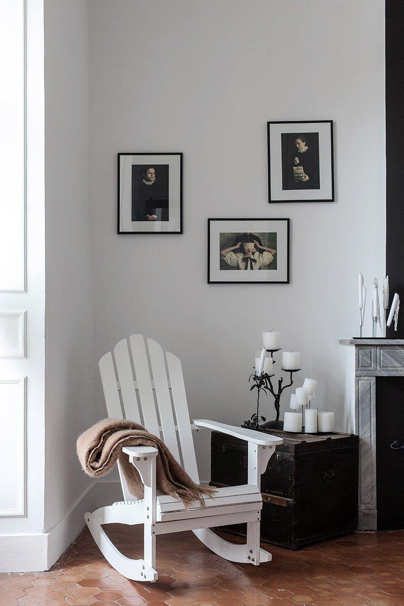 Ambiance déco - rocking chair en bois blanc avec son plaid, bougies, devant la cheminée © Denis Dalmasso